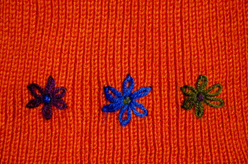 knited wool background with flower symbols