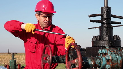 Oil Worker in Action at Oil Well