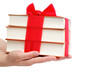 Book as a gift. A stack of books in female hands on a white back