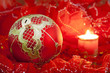 Christmas red bauble and candle on blurred background