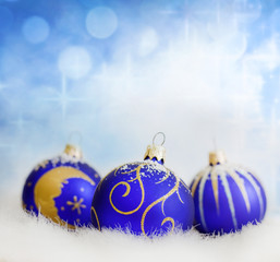Christmas blue baubles on abstract blurred background closeup