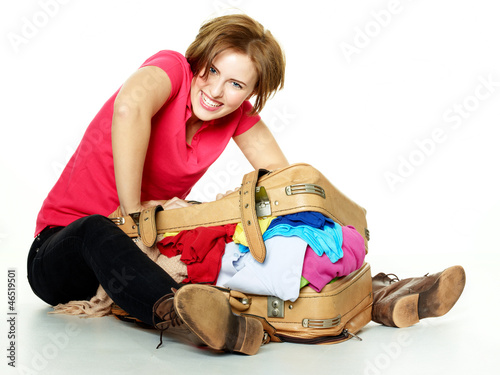 Pretty woman packs her overcrowded bag for holidays