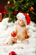 Christmas baby in hat sitting on fur holding red ball