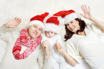 Christmas family in red hats. Hapy parents and baby