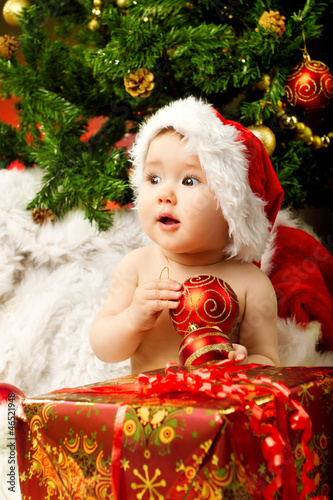 Christmas baby holding red gift