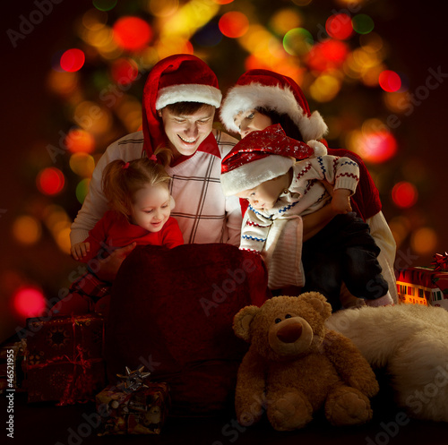 Christmas family opening lighting bag with gifts