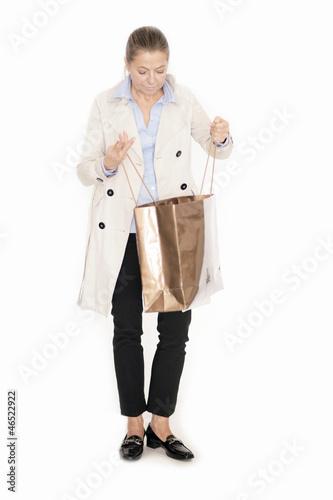 Elegante Dame blickt neugierig in ihre Einkaufstüte