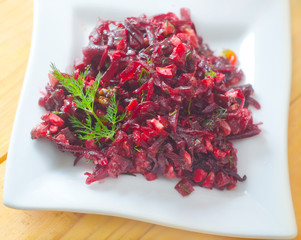 Fresh salad with beet and walnuts on white plate