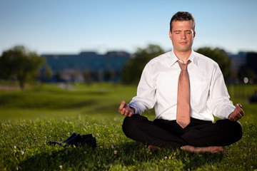 Barefoot businessman meditating in a beautiful park