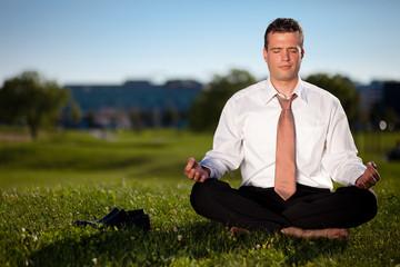 Barefoot businessman meditating in a beautiful park