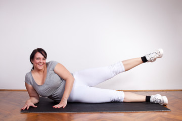 Smiling overweight woman exercising