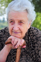 senior woman sittingby leaning her stick / cane