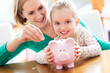 Leinwanddruck Bild - Mother and daughter with piggy bank