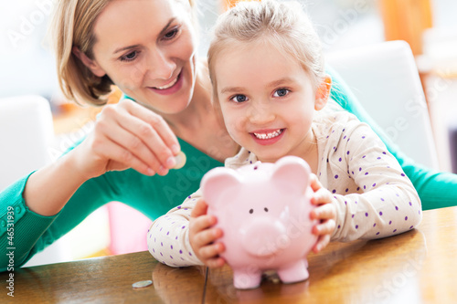 Leinwanddruck Bild Mother and daughter with piggy bank