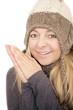Frau mit Wollmütze reibt sich die kalten Hände