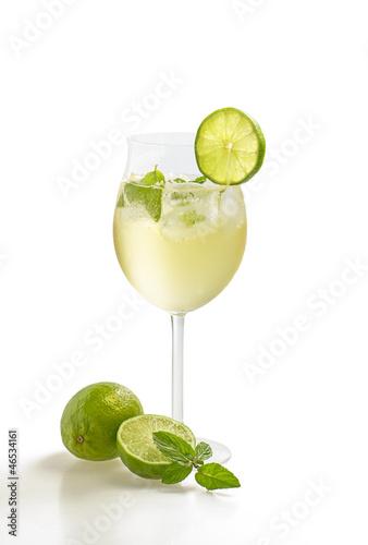 Aperitif mit Limetten und Minze in einem Weinglas