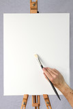 Artist holding brush on blank canvas ready for customizarion poster