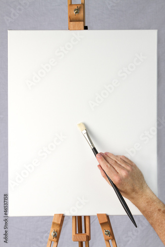 Artist holding brush on blank canvas ready for customizarion