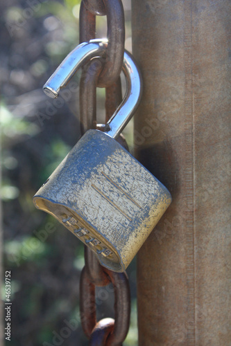 Open combination lock hanging on chain