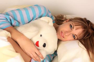 Adulto joven durmiendo con oso de peluche