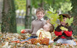 three happy children - boy, girl and baby - on natural autumn ba