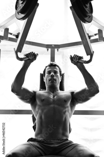 bodybuilder hard taining in the gym: shoulder press