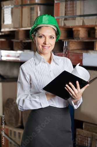 Confident Female Supervisor With Book At Warehouse