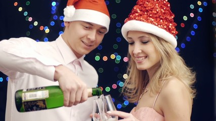 man pouring champagne with woman near by at christmas party