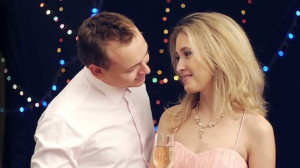 Handsome man brings champagne to girlfriend  at party