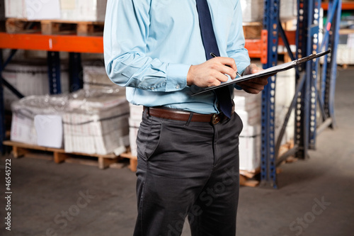 Supervisor Writing On Clipboard At Warehouse