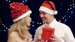 Happy  woman giving present to boyfriend at christmas party