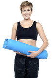 Health conscious woman holding blue exercise mat poster
