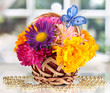 Beautiful bouquet of bright flowers in small basket with paper