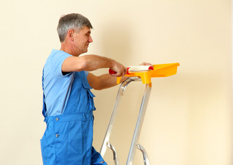 Male painter paints wall in room close-up