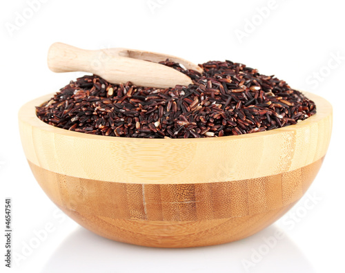 black rice in a  brown wooden plat with a wooden scoop,