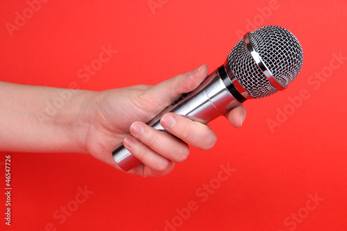 Silver microphone in hand on red background