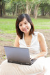 Asian woman smiling with laptop sitting at park