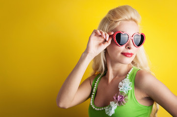 Blonde girl with heart glasses against yellow background.