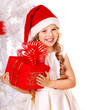 Child in Santa hat with gift box near white Christmas tree.