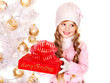 Child in hat and mittens holding  Christmas red gift box .