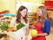 Verkäuferin zeigt Kundin eine Honigmelone