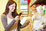 Frau scannt Barcode im Supermarkt