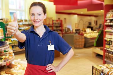 Ältere Supermarkt-Mitarbeiterin hält Daumen hoch