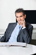 Confident Businessman Sitting At Desk