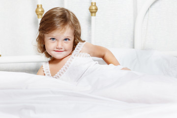Toddler covered with white blanket