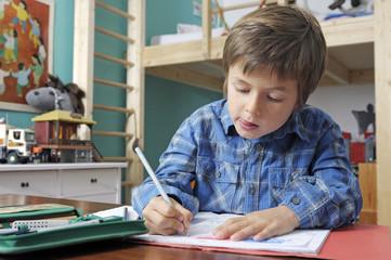 Kind konzentriert bei den Hausaufgaben