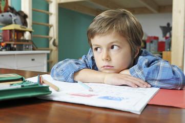 Kind träumt bei den Hausaufgaben