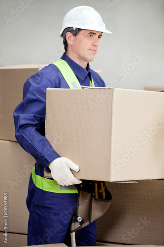 Foreman Lifting Cardboard Box At Warehouse