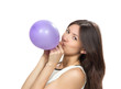 Young happy girl blowing balloons for birthday party