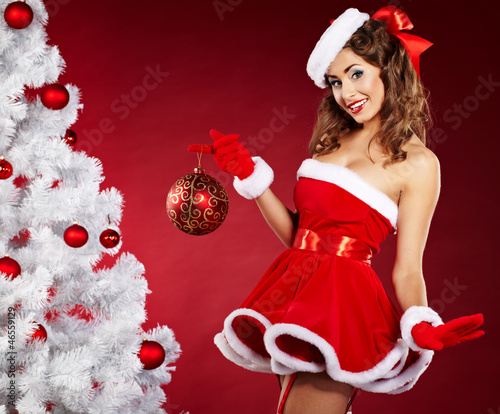 smiling christmas woman on red background with a christmas-tree
